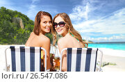 Купить «happy young women with drinks sunbathing on beach», фото № 26547086, снято 11 июля 2013 г. (c) Syda Productions / Фотобанк Лори