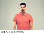 Купить «surprised man in polo t-shirt over gray background», фото № 26549046, снято 15 января 2016 г. (c) Syda Productions / Фотобанк Лори