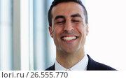 Купить «smiling businessman touching his hair at office», видеоролик № 26555770, снято 26 июня 2019 г. (c) Syda Productions / Фотобанк Лори