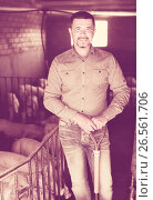 Man farmer standing in pigsty. Стоковое фото, фотограф Яков Филимонов / Фотобанк Лори