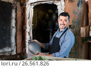 Купить «gay male with black-glazed ceramic vase standing close to kiln», фото № 26561826, снято 16 июня 2019 г. (c) Яков Филимонов / Фотобанк Лори