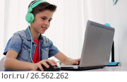 Купить «boy in headphones playing video game on laptop», видеоролик № 26562262, снято 23 мая 2019 г. (c) Syda Productions / Фотобанк Лори