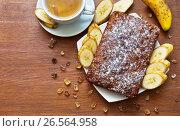 Купить «Домашний банановый кекс с сахарной пудрой, кусочки банана и компот из сухофруктов на деревянном столе», фото № 26564958, снято 21 июня 2017 г. (c) Виктория Катьянова / Фотобанк Лори