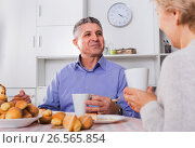 Купить «Mature couple have an afternoon snack with fresh muffins and cake», фото № 26565854, снято 27 мая 2019 г. (c) Яков Филимонов / Фотобанк Лори