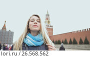 Купить «Beautiful blond girl posing against a red square in Moscow. Russia.», видеоролик № 26568562, снято 10 июня 2017 г. (c) Mikhail Davidovich / Фотобанк Лори