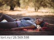 Купить «Young couple napping on mat at olive farm», фото № 26569598, снято 22 марта 2017 г. (c) Wavebreak Media / Фотобанк Лори