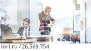 Купить «Businessman talking on a mobile phone on corporate office», фото № 26569754, снято 12 мая 2017 г. (c) Matej Kastelic / Фотобанк Лори