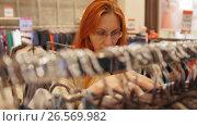 Купить «Attractive girl in a clothing store chose a dress - shopping concept», видеоролик № 26569982, снято 18 января 2020 г. (c) Константин Шишкин / Фотобанк Лори