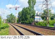 Купить «Поворот железнодорожных путей и строительный башенный подъемный кран на заднем плане», фото № 26570226, снято 7 июня 2017 г. (c) Александр Замараев / Фотобанк Лори