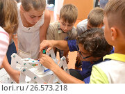 "SOCHI, RUSSIA - June 24, 2017: Teacher helps schoolchildren to design a robot in an open lesson on robotics of the All-Russian Educational Center ""Sirius"" Редакционное фото, фотограф Анна Мартынова / Фотобанк Лори"