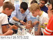 """Купить «SOCHI, RUSSIA - June 24, 2017: Middle-aged students with a teacher complete the construction of a robot in an open lesson of the All-Russian Educational Center """"Sirius""""», фото № 26573222, снято 24 июня 2017 г. (c) Анна Мартынова / Фотобанк Лори"""