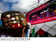 Купить «Пилотка со значками иностранного футбольного болельщика на фоне баннера Кубка конфедераций FIFA 2017 на фасаде стадиона «Открытие Арена» в городе Москве, Россия», фото № 26574514, снято 25 июня 2017 г. (c) Николай Винокуров / Фотобанк Лори