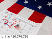 Calendar marked with star shape decoration and American flag. Стоковое фото, агентство Wavebreak Media / Фотобанк Лори