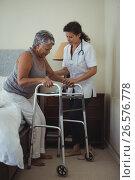 Купить «Female doctor helping senior woman to walk with walker», фото № 26576778, снято 20 марта 2017 г. (c) Wavebreak Media / Фотобанк Лори