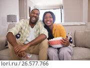 Купить «Cheerful young couple watching television while sitting on sofa at home», фото № 26577766, снято 15 марта 2017 г. (c) Wavebreak Media / Фотобанк Лори