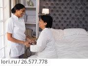Smiling nurse comforting mature woman on bed. Стоковое фото, агентство Wavebreak Media / Фотобанк Лори