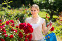 merry young woman working with bush roses with horticultural tools in garden, фото № 26580158, снято 27 июня 2017 г. (c) Яков Филимонов / Фотобанк Лори