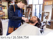 Купить «man and barber with trimmer cutting beard at salon», фото № 26584754, снято 6 апреля 2017 г. (c) Syda Productions / Фотобанк Лори
