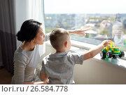 Купить «mother and son looking through window at home», фото № 26584778, снято 22 мая 2017 г. (c) Syda Productions / Фотобанк Лори