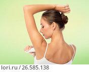 Купить «woman with antiperspirant deodorant over white», фото № 26585138, снято 9 апреля 2017 г. (c) Syda Productions / Фотобанк Лори
