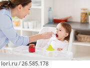 Купить «happy mother feeding baby with puree at home», фото № 26585178, снято 24 января 2017 г. (c) Syda Productions / Фотобанк Лори