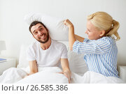 Купить «happy couple having pillow fight in bed at home», фото № 26585386, снято 11 февраля 2017 г. (c) Syda Productions / Фотобанк Лори