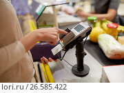 Купить «woman entering pin code at store cash register», фото № 26585422, снято 21 октября 2016 г. (c) Syda Productions / Фотобанк Лори