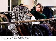 Купить «Female customer examining patterned fir jacket», фото № 26586690, снято 8 июля 2020 г. (c) Яков Филимонов / Фотобанк Лори