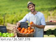 Portrait of smiling man standing by fresh fruits in wicker basket. Стоковое фото, агентство Wavebreak Media / Фотобанк Лори