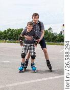 Купить «Отец придерживает сына во время катания на роликовых коньках», фото № 26588294, снято 18 июня 2017 г. (c) Кекяляйнен Андрей / Фотобанк Лори