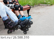 Купить «Роликовые коньки для катания в парке на ногах, люди сидят на скамейке», фото № 26588310, снято 18 июня 2017 г. (c) Кекяляйнен Андрей / Фотобанк Лори