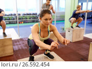 Купить «woman doing box jumps at group training in gym», фото № 26592454, снято 19 февраля 2017 г. (c) Syda Productions / Фотобанк Лори