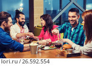 friends eating and tasting food at restaurant. Стоковое фото, фотограф Syda Productions / Фотобанк Лори