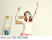 Купить «happy woman in headphones ihaving fun at home», фото № 26592566, снято 14 ноября 2015 г. (c) Syda Productions / Фотобанк Лори