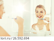 Купить «woman with toothbrush cleaning teeth at bathroom», фото № 26592694, снято 13 февраля 2016 г. (c) Syda Productions / Фотобанк Лори