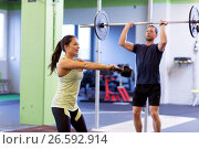 Купить «man and woman with weights exercising in gym», фото № 26592914, снято 19 февраля 2017 г. (c) Syda Productions / Фотобанк Лори