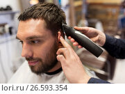 Купить «man and barber hands with trimmer cutting hair», фото № 26593354, снято 6 апреля 2017 г. (c) Syda Productions / Фотобанк Лори