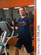 Happy smiling senior man exercising on machine. Стоковое фото, фотограф Pavel Biryukov / Фотобанк Лори