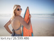 Купить «Portrait of smiling woman holding surfboard at beach», фото № 26599486, снято 1 марта 2017 г. (c) Wavebreak Media / Фотобанк Лори