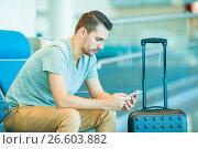 Купить «Young man in an airport lounge waiting for flight aircraft. Caucasian man with smartphone in the waiting room», фото № 26603882, снято 9 июня 2017 г. (c) Дмитрий Травников / Фотобанк Лори