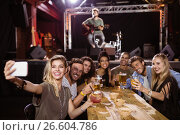 Купить «cheerful friends taking selfie while sitting at table with performer singing on stage», фото № 26604786, снято 7 марта 2017 г. (c) Wavebreak Media / Фотобанк Лори