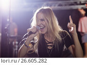 Купить «Happy young female singer performing at nightclub», фото № 26605282, снято 7 марта 2017 г. (c) Wavebreak Media / Фотобанк Лори