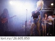 Купить «Young singer with tousled long hair performing at nightclub», фото № 26605850, снято 7 марта 2017 г. (c) Wavebreak Media / Фотобанк Лори