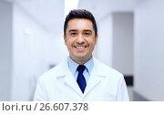 Купить «smiling doctor in white coat at hospital», фото № 26607378, снято 3 декабря 2015 г. (c) Syda Productions / Фотобанк Лори