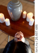 Купить «sad woman with funerary urn praying at church», фото № 26607686, снято 20 марта 2017 г. (c) Syda Productions / Фотобанк Лори