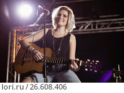Portrait of smiling female guitarist playing guitar at nightclub. Стоковое фото, агентство Wavebreak Media / Фотобанк Лори