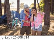 Купить «Smiling couple listening music on headphone while standing against trees», фото № 26608714, снято 9 марта 2017 г. (c) Wavebreak Media / Фотобанк Лори