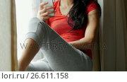 Woman sitting on windowsill and using mobile phone. Стоковое видео, агентство Wavebreak Media / Фотобанк Лори