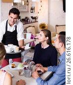 Купить «smiling waiter bringing ordered dishes to friends in tearoom», фото № 26616178, снято 5 июня 2017 г. (c) Яков Филимонов / Фотобанк Лори