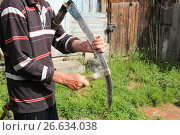 Купить «Man sharpening a scythe before mowing», фото № 26634038, снято 23 июня 2017 г. (c) Константин Шишкин / Фотобанк Лори